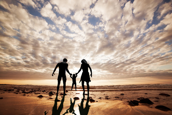 Happy family together hand in hand on the beach at sunset. Summer time, parents, child Stock photo © photocreo