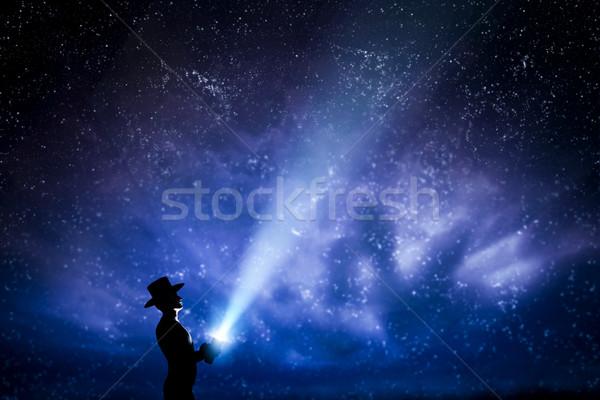 Man in hat throwing light beam up the night sky full of stars. To explore, dream, magic. Stock photo © photocreo