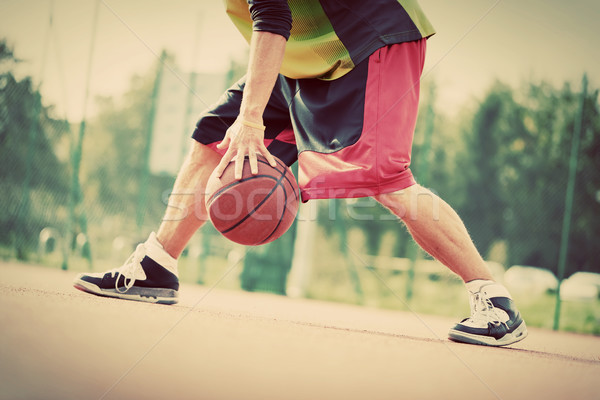 Young man on basketball court dribbling with ball. Vintage mood Stock photo © photocreo