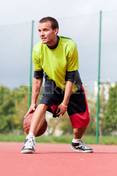 Young man on basketball court dribbling with ball Stock photo © photocreo