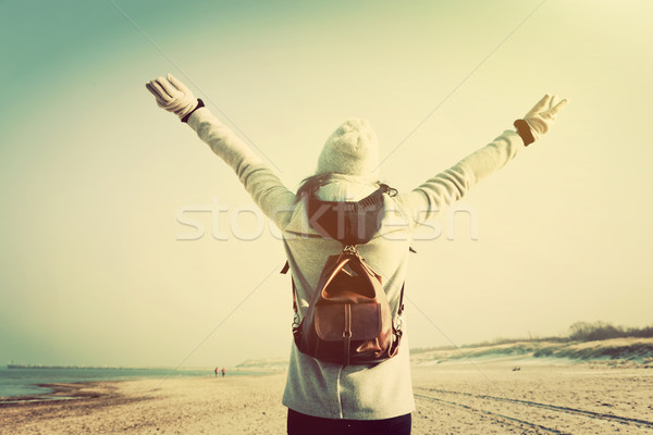 Woman with hands up wearing retro backpack on the beach Stock photo © photocreo