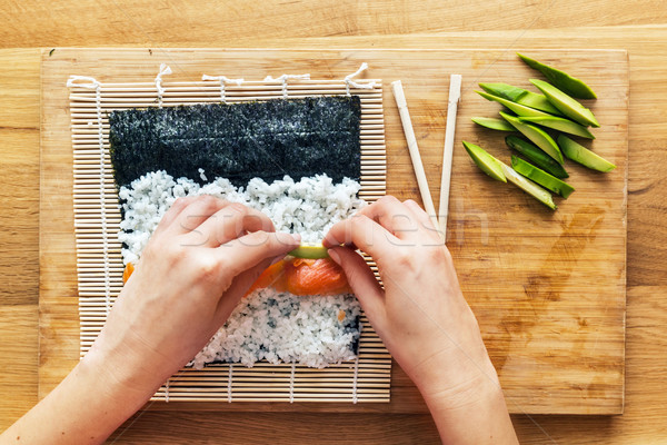 Stock photo: Preparing sushi. Salmon, avocado, rice and chopsticks on wooden table.