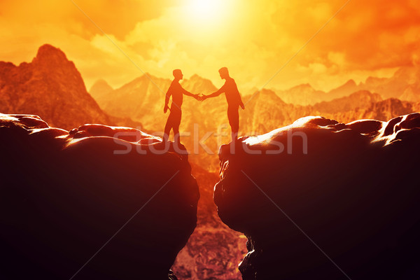 Stock photo: Two men shake hands over precipice. Business, handshake, deal.