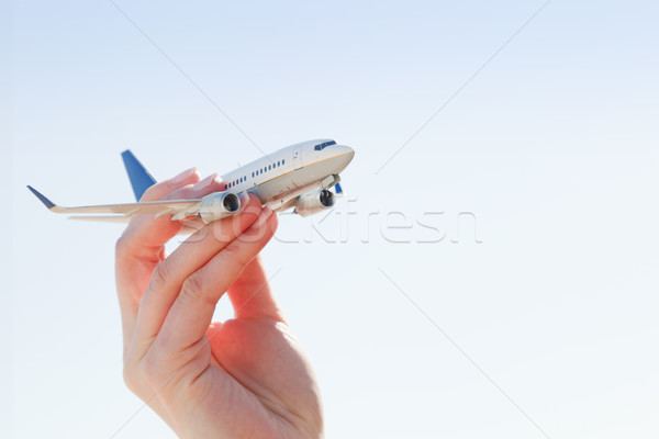 Airplane model in hand on sunny sky. Concepts of travel, transportation Stock photo © photocreo