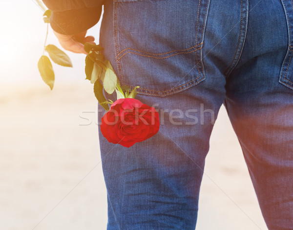 Stock photo: Man with a rose behind his back waiting for love. Romantic date on the beach