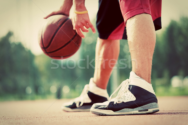 Young man on basketball court dribbling with bal Stock photo © photocreo