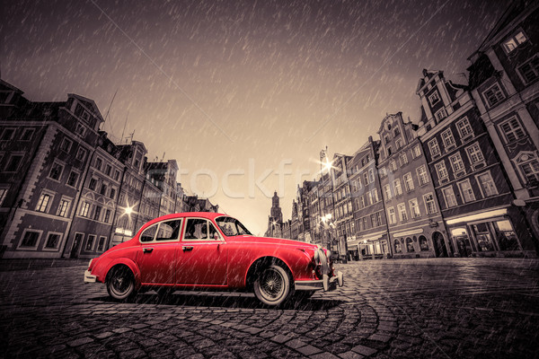 Retro red car on cobblestone historic old town in rain. Wroclaw, Poland. Stock photo © photocreo