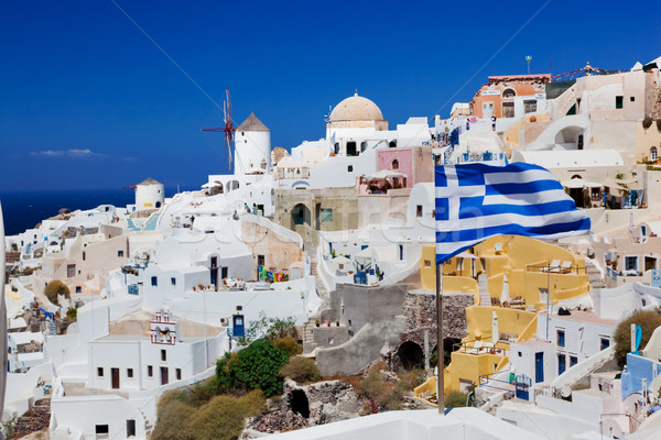 Oia town on Santorini island, Greece. Waving Greek flag Stock photo © photocreo