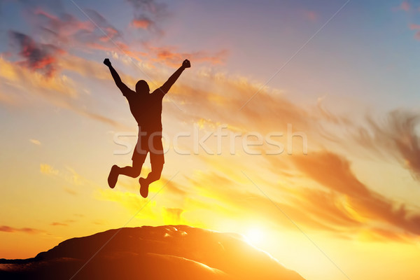 Happy man jumping for joy on the peak of the mountain at sunset. Success Stock photo © photocreo