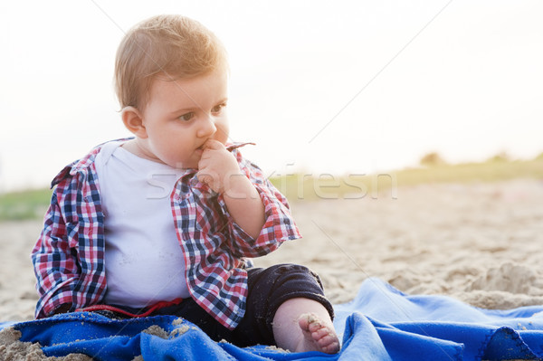 Handsome curious child sitting on sand on the beach playing Stock photo © photocreo