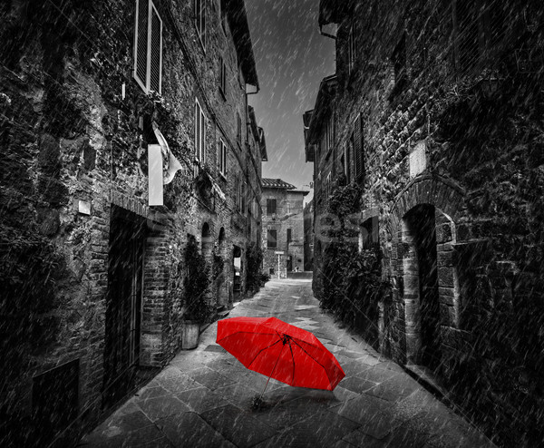 Umbrella on dark street in an old Italian town in Tuscany, Italy. Raining. Stock photo © photocreo