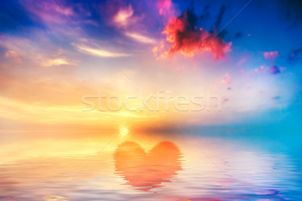 Heart shape in calm ocean at sunset. Beautiful sky Stock photo © photocreo
