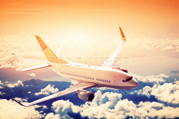 Airplane in flight. A big passenger or cargo aircraft, airline above clouds. Stock photo © photocreo