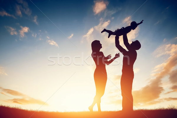 Stock photo: Happy family together, parents with their little child at sunset.