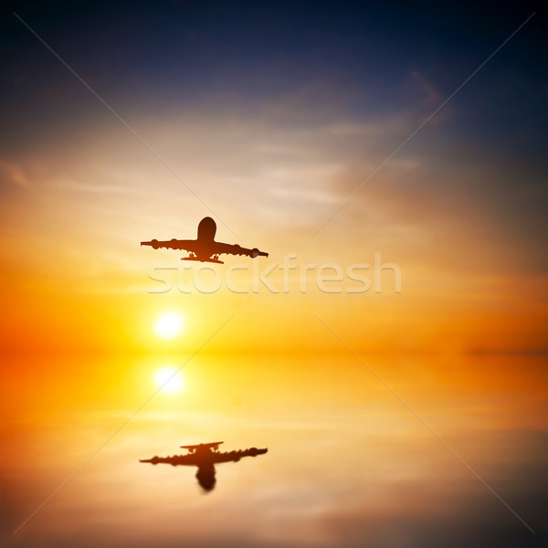 Airplane taking off at sunset. Silhouette of a passenger or carg Stock photo © photocreo