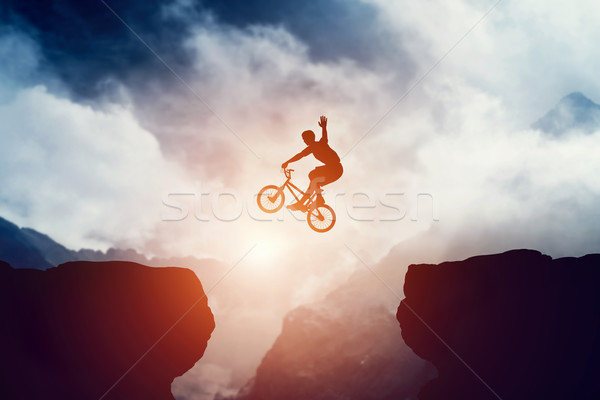 Stock photo: Man jumping on bmx bike over precipice in mountains at sunset.