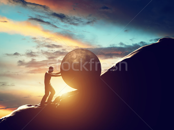 Sisyphus metaphor. Man rolling huge concrete ball up hill. Stock photo © photocreo