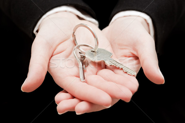 A real estate agent holding keys to a new house in her hands. Stock photo © photocreo