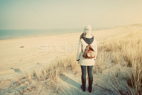Woman with retro backpack on the beach looking at the sea Stock photo © photocreo