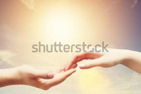 Soft, gentle touch of man and woman against sunny sky with flare in vintage mood. Stock photo © photocreo