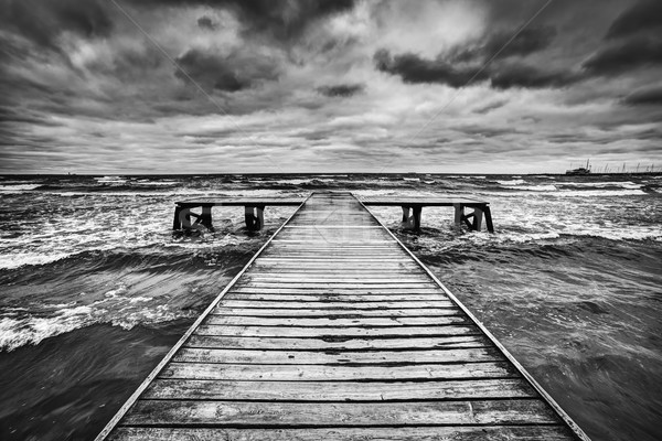 Old wooden jetty during storm on the sea. Dramatic sky with dark, heavy clouds Stock photo © photocreo