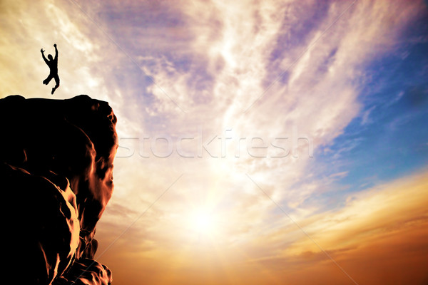 A silhouette of a man jumping for joy on the peak of the mountain, cliff at sunset Stock photo © photocreo