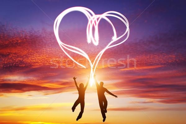 Happy couple in love jump making heart symbol of light Stock photo © photocreo