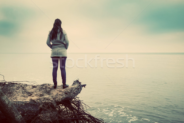 Woman standing on broken tree on wild beach looking at sea horizon Stock photo © photocreo