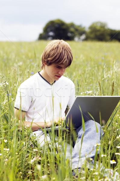 Zdjęcia stock: Chłopca · notebooka · dziedzinie · zewnątrz · niebo · moda