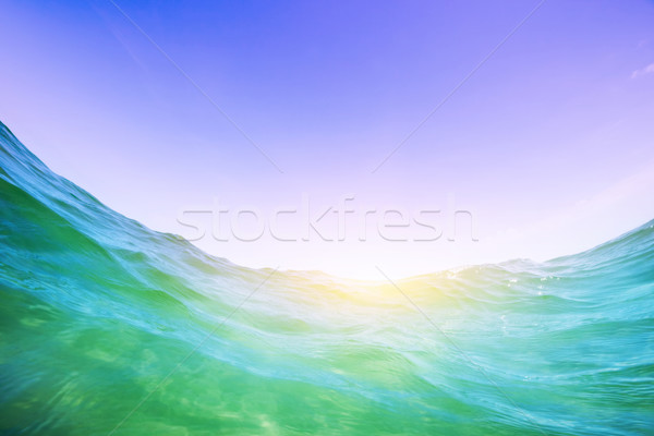 Water wave in the ocean. Underwater and blue sunny sky. Stock photo © photocreo