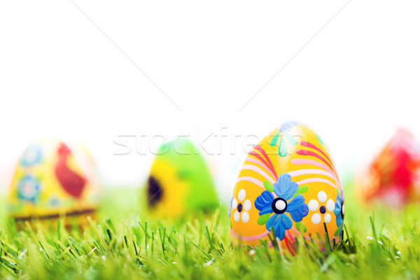 Colorful hand painted Easter eggs in grass. Spring theme, white copy-space Stock photo © photocreo