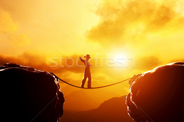 Man in hat walking, balancing on rope over mountains at sunset Stock photo © photocreo