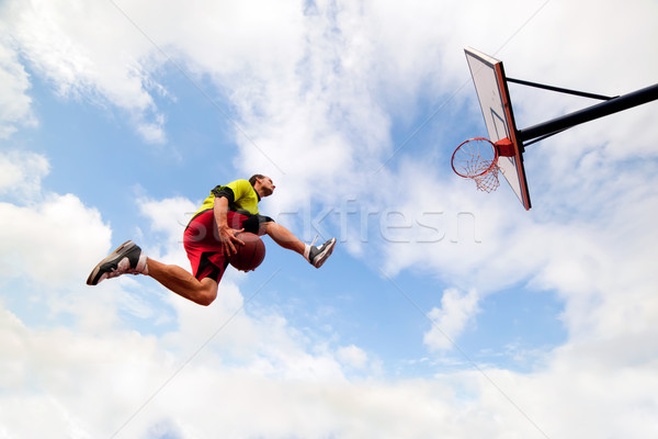 Young man making a fantastic slam dunk playing streetball, basketball Stock photo © photocreo