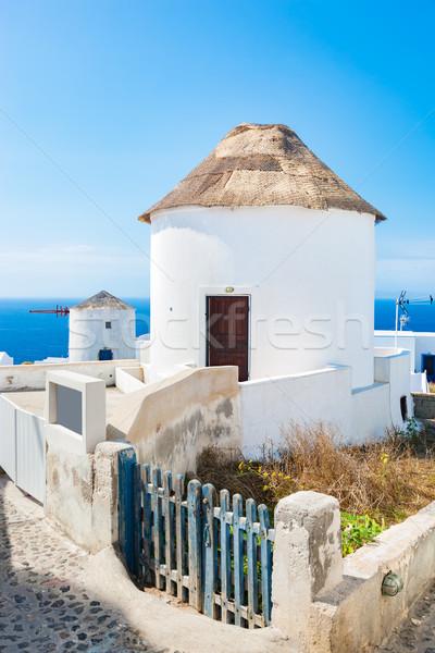 Famous windmills in Oia town on Santorini island, Greece. Stock photo © photocreo