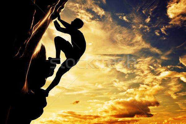 A silhouette of man free climbing on rock, mountain at sunset. A Stock photo © photocreo