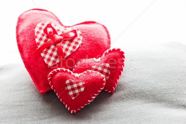Handmade plush red hearts on the soft pillow. Romantic love Stock photo © photocreo
