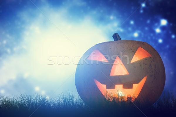 Halloween pumpkin glowing in dark, misty scenery under night sky and moon Stock photo © photocreo