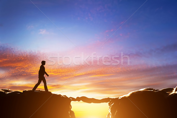 Man walking over precipice between mountains, another man being a bridge Stock photo © photocreo