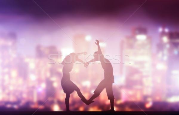 Happy couple in love making heart shape. City at night Stock photo © photocreo