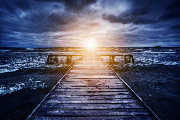 Old wooden jetty during storm on the ocean. Abstract light at the end Stock photo © photocreo