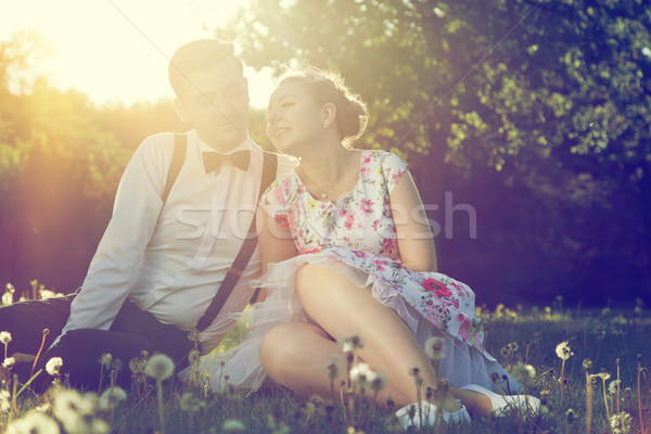 Romantic couple in love flirting on grass in sunny park. Vintage Stock photo © photocreo