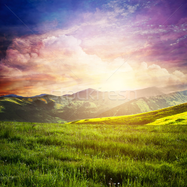 Fairtytale landscape with green grass, mountains, sunset fantastic sky. Stock photo © photocreo