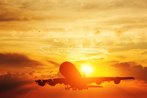 Airplane taking off at sunset. Silhouette of a flying passenger or cargo aircraft, airline Stock photo © photocreo