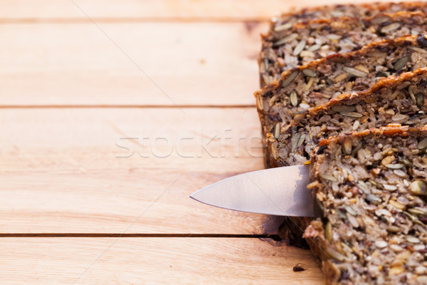 Stock photo: Knife in wholemeal, wholewheat bread on wooden table. Organic, healthy food