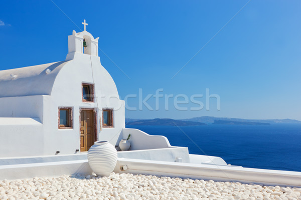 Oia town on Santorini island, Greece. White church and vase. Stock photo © photocreo
