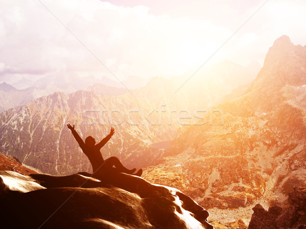 A happy man sitting on the peak of a mountain with hands raised at sunset Stock photo © photocreo