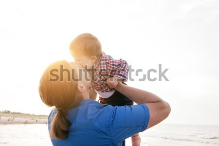 Young father holding his child on the beach and kissing with love Stock photo © photocreo