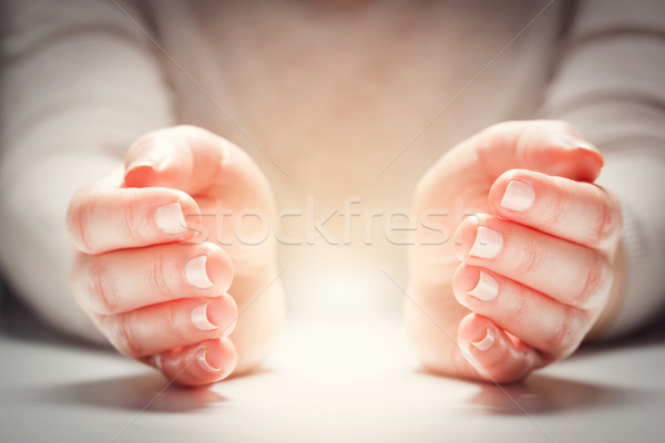 Light between woman's hands in gesture of protection, care. Stock photo © photocreo