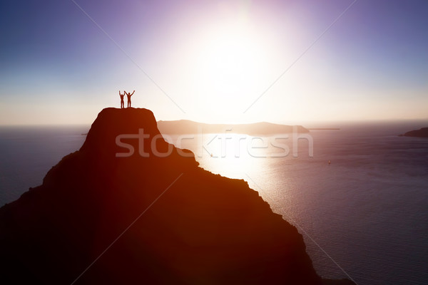 Happy couple on the top of the mountain over ocean celebrating life, success Stock photo © photocreo
