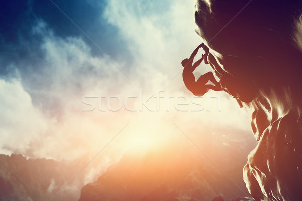 A silhouette of man climbing on rock, mountain at sunset.  Stock photo © photocreo